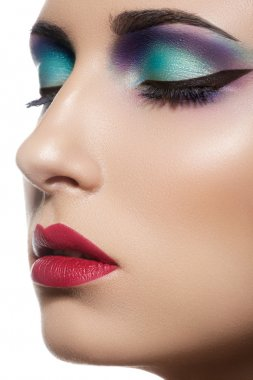 Closeup beauty portrait of attractive model face with bright visage. Multicolored eye makeup and vinous lips make-up