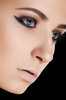 Beauty, cosmetics and fashion. Beautiful woman model face with clean skin, liner eye makeup, pale lips make-up on black background