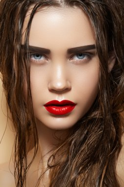 Hot young woman model with sexy bright red lips makeup, strong eyebrows, clean shiny skin and wet hairstyle. Beautiful fashion portrait of glamour female face