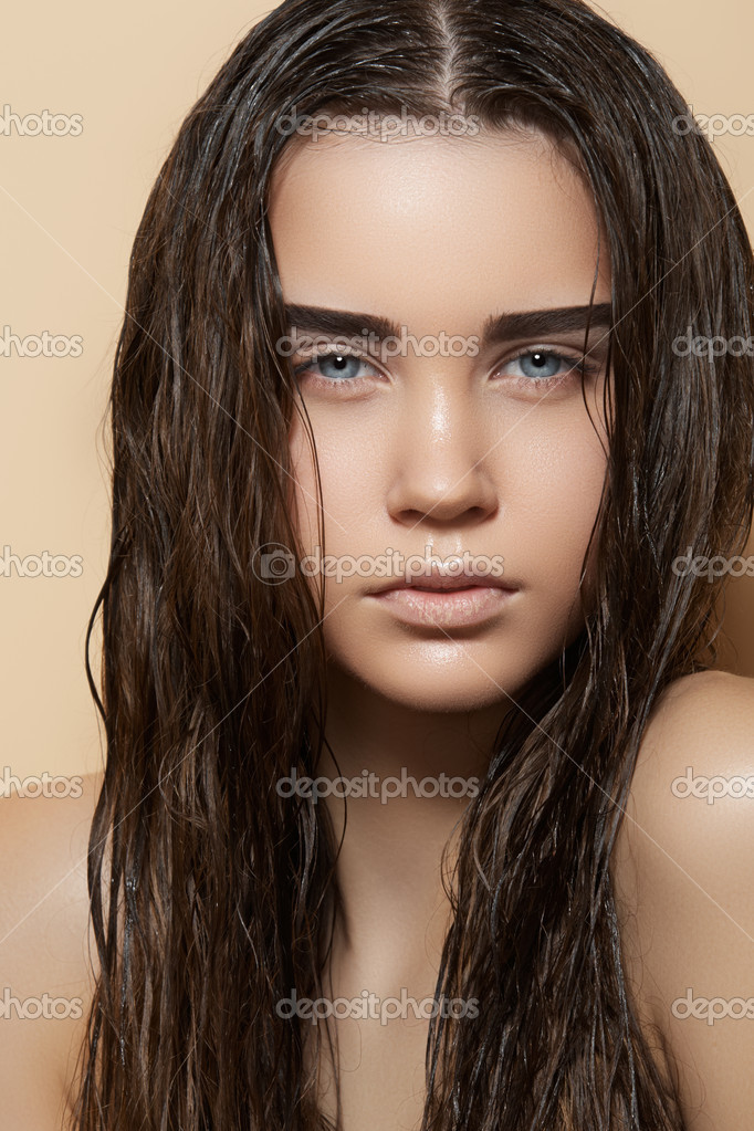 Beautiful young model with long wet hair, light makeup, strong eyebrows and perfect purity skin. Fresh summer look with damp beach hairstyle
