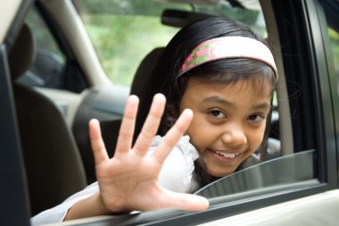 Child waving goodbye from inside a car