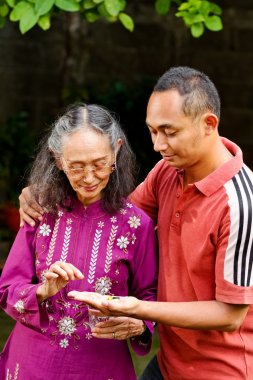 Asian young man embrace and help elderly mother taking medicine