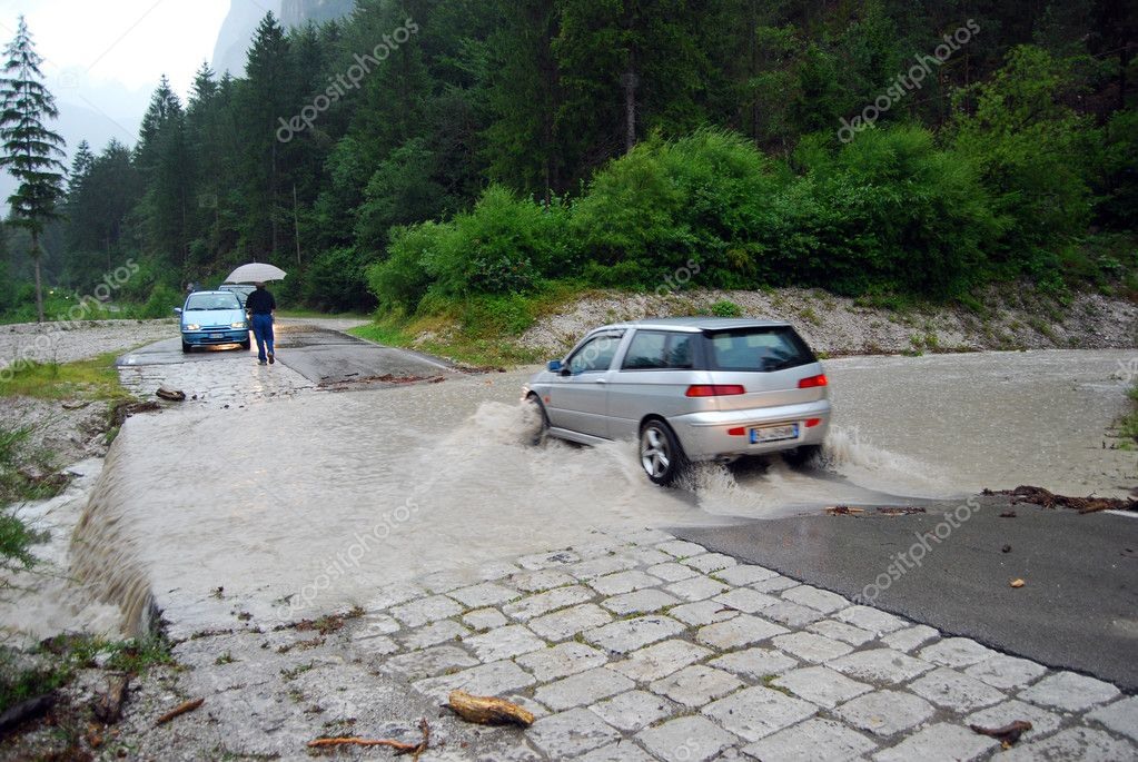 Car crossing a road flooded