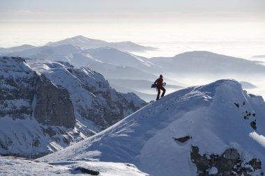 Man climbing a peak with snowboard