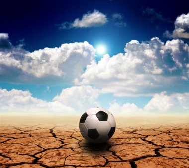 Soccer ball on a dry desert land against a blue sky with clouds stock vector