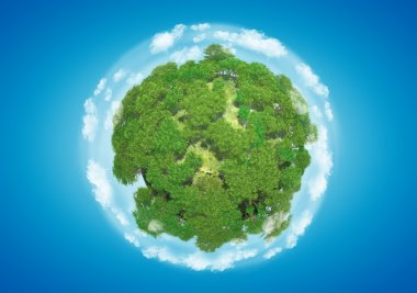 Miniature planet with sparse leafy tree vegetation and clouds on blue sky