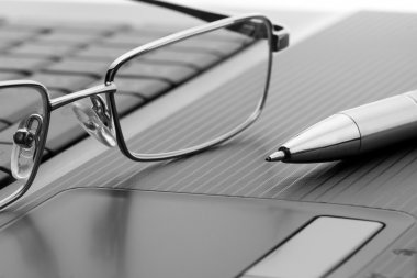 Glasses and pen on laptop