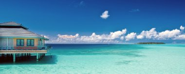 Tropical beach panorama with water hut and distant island on the maldives