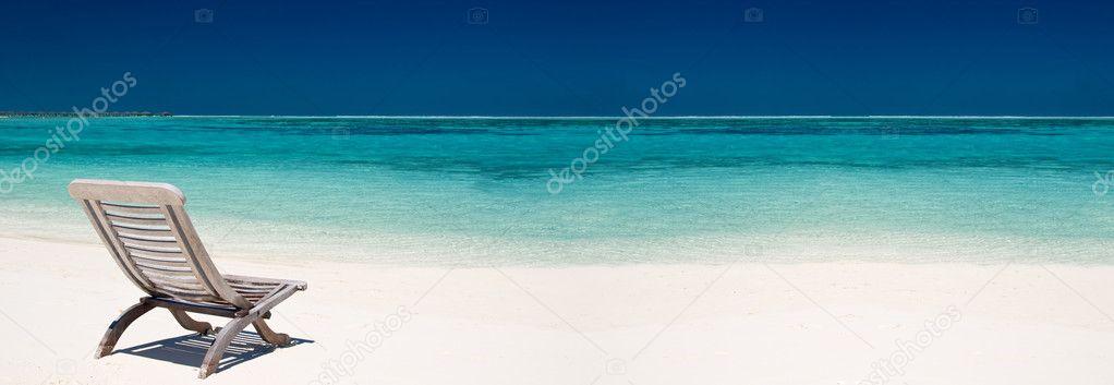 Wooden canvas chair on a beautiful tropical beach