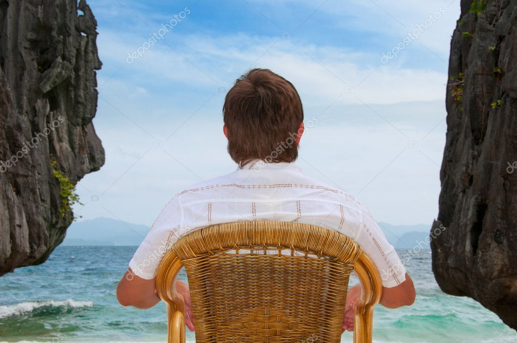 Meditating man sitting at the beach between rocks looking at the sea