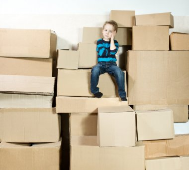 Child sitting on the top of heap of carton packed boxes.
