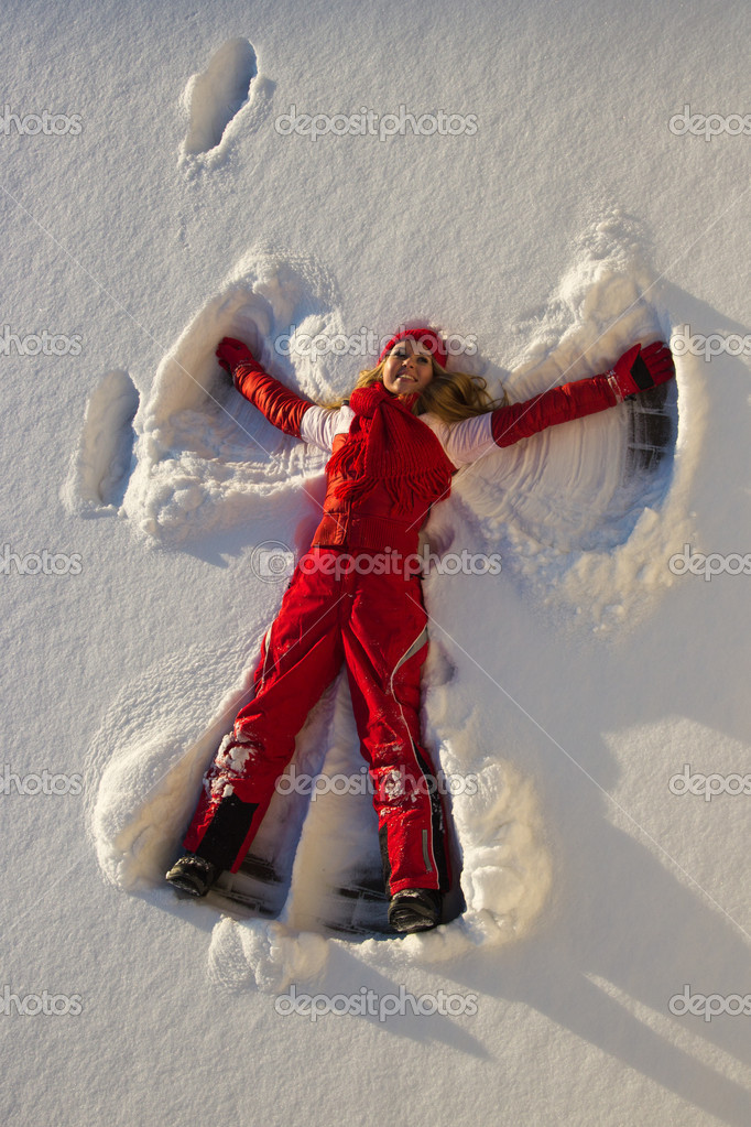 Woman making an angel on snow
