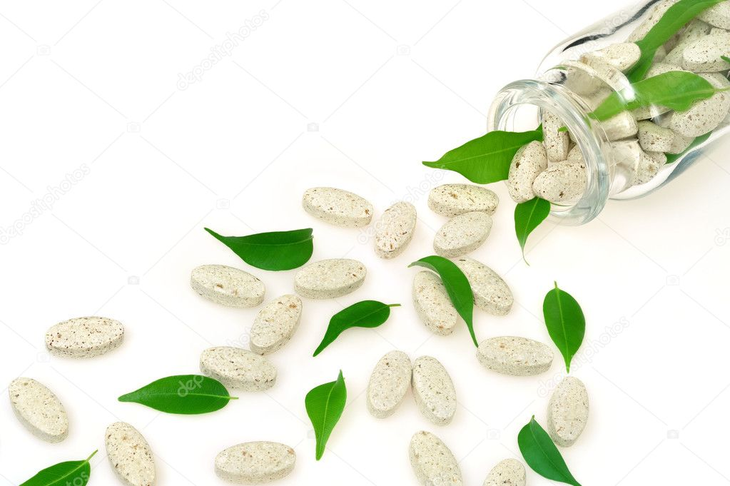 Herbal supplement pills and fresh leaves spilling out of bottle – alternat