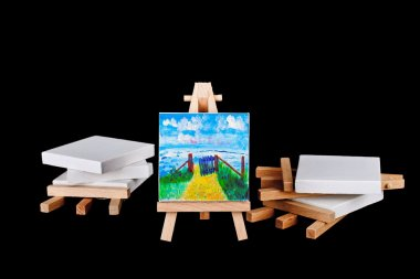 Artists easels stacked on a black background