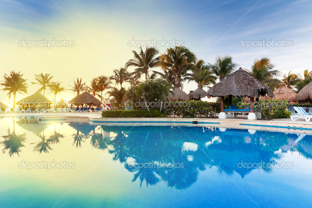 Tropical swimming pool at sunrise