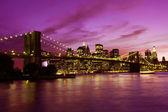 Fotografie Brooklyn bridge a manhattan při západu slunce, new york