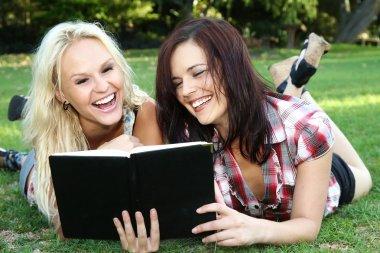 Beautiful Young Women Friends Reading Outdoors