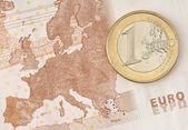 jedno euro mince na eurobankovky zobrazující mapu Evropy