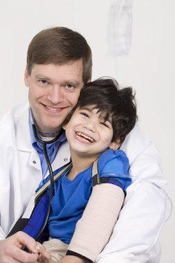 Male doctor holding disabled toddler patient on lap