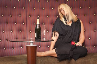 Sensual Blonde Woman Sitting Near Champagne and Rose