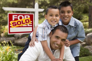 Hispanic Father and Sons in Front of Sold Real Estate Sign