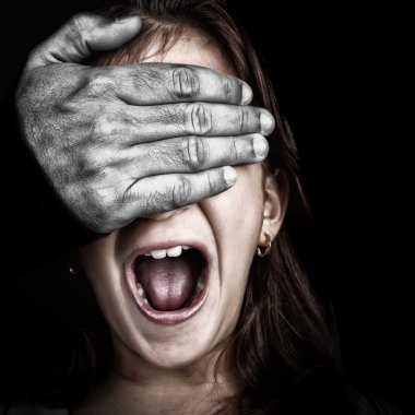 Girl screaming while a hairy hand covers her eyes