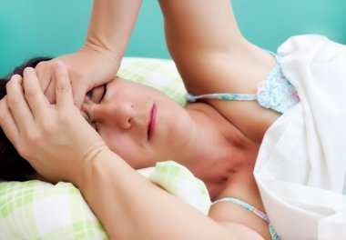 Hispanic woman suffering from a strong headache