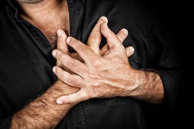 Close up of two hands grabbing a chest on a black background, useful to represent a heart attack or any sentimental concept stock vector
