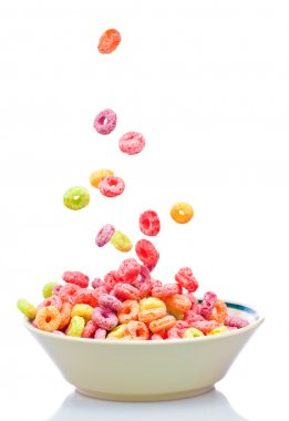 Colorful cereal falling on a bowl isolated on white