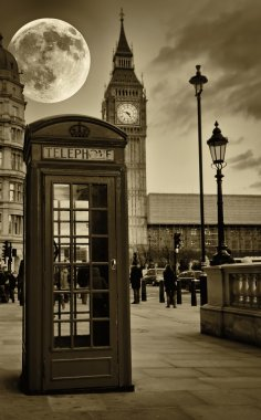 Vintage sepia image of the Big Ben in London with a typical red phone booth
