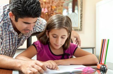 Young latin gather helping her daughter with homework