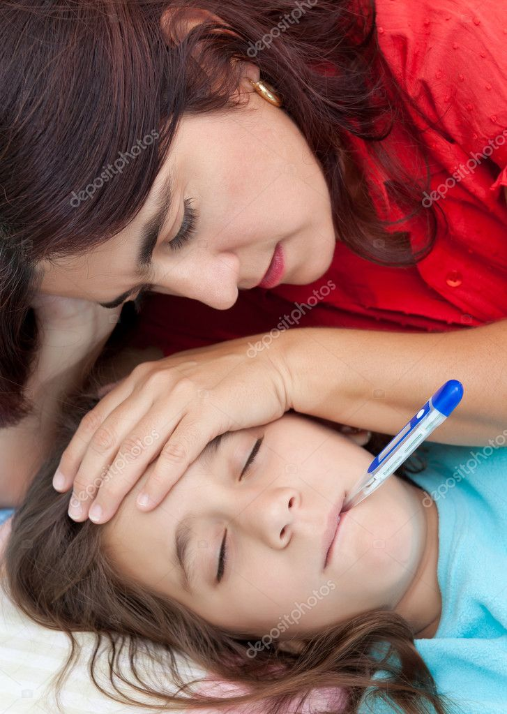 Hispanic mother checking the temperature of her sick little girl