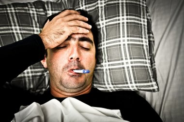 Dramatic image of a sick man in bed with fever