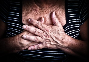 Aged woman's hands over her chest