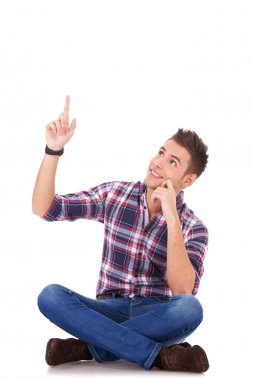 Seated young casual man pointing at something up