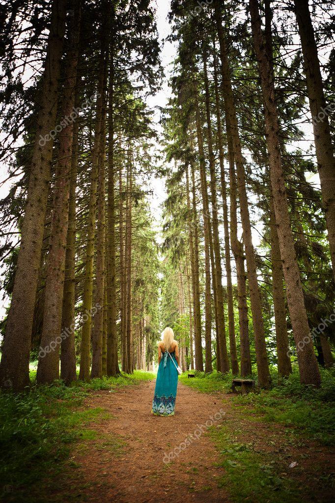 Woman walking in the fir woods