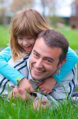 Father and daughter having fun in the grass on beautiful spring day