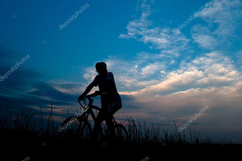 Silhouette of the man riding the bicycle at dusk