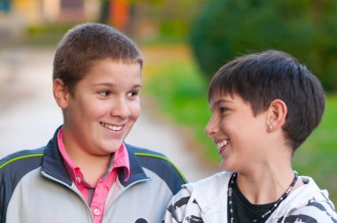 Two teenage boys laughing and kidding in the park on beautiful autumn day