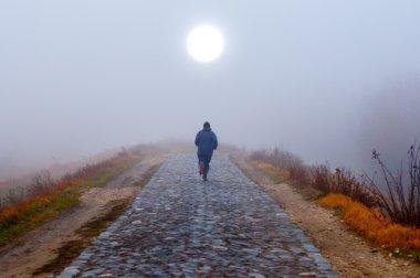 Lonely man running toward the sun on misty autumn morning