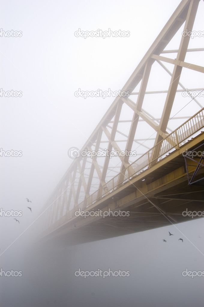 Yellow bridge disappears in the thick autumn fog