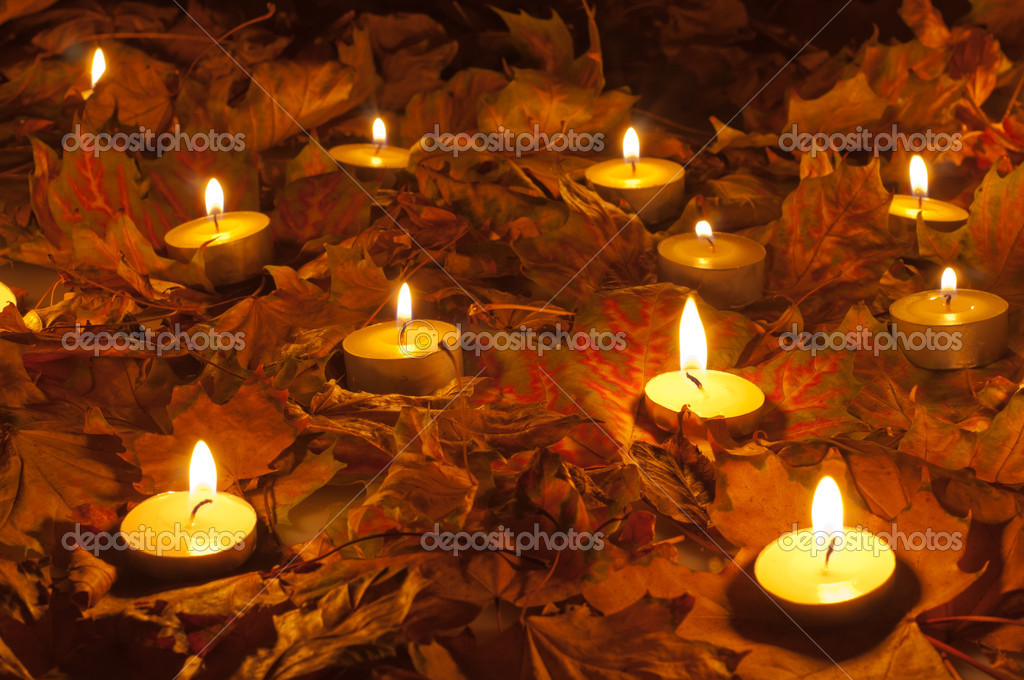 Candle flames lighting the bed of dry leaves on beautiful autumn night