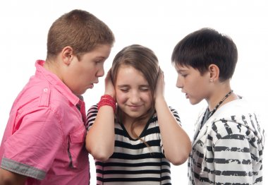 Two angry teenage boys harassing frightened girl