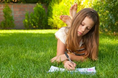 Cute teenage girl lies on the grass and draws in her notebook
