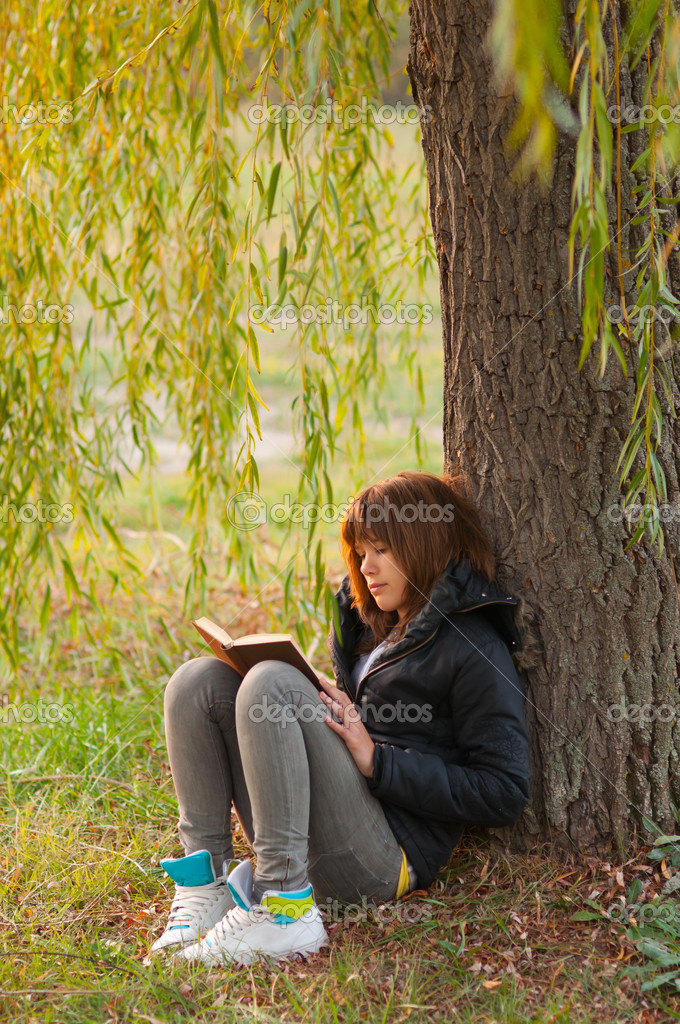 Pretty teenage girl reads the book under the willow tree