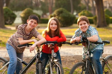 Two smiling teenage boys and one teenage girl having fun on bicycles in the park