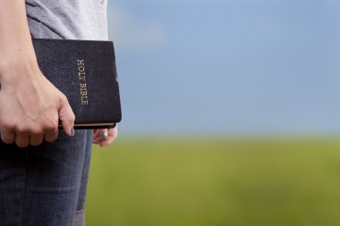 Standing Holding the Bible in a Field