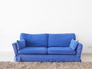 Double couch on a blank wall