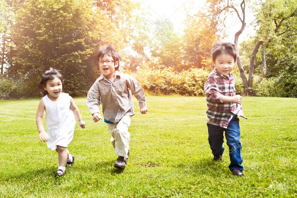Asian kids running in park