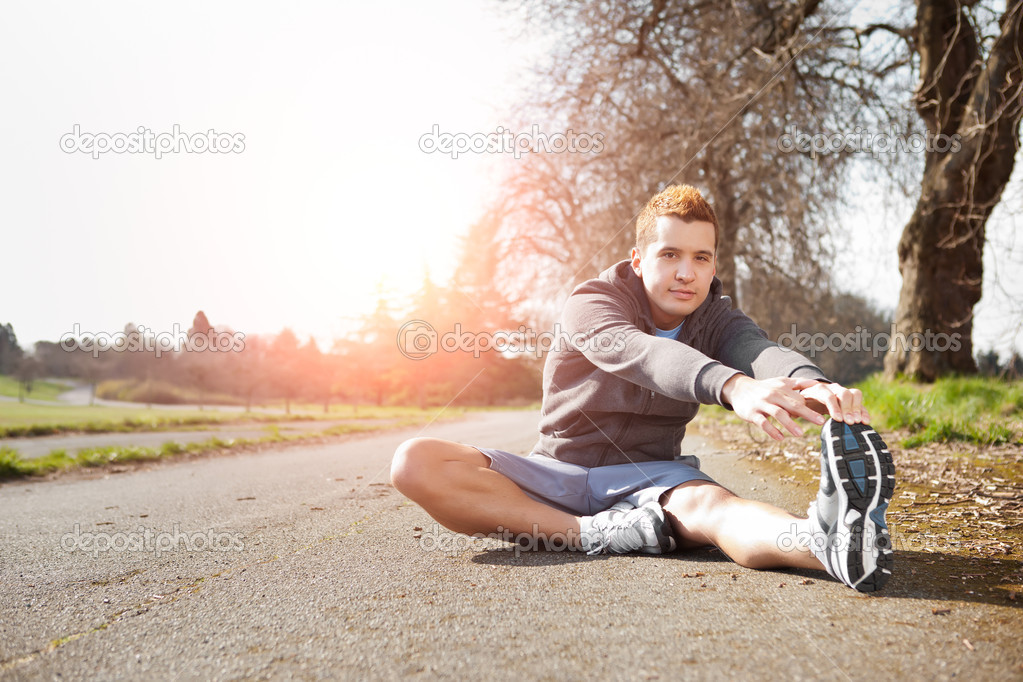 Mixed race man stretching